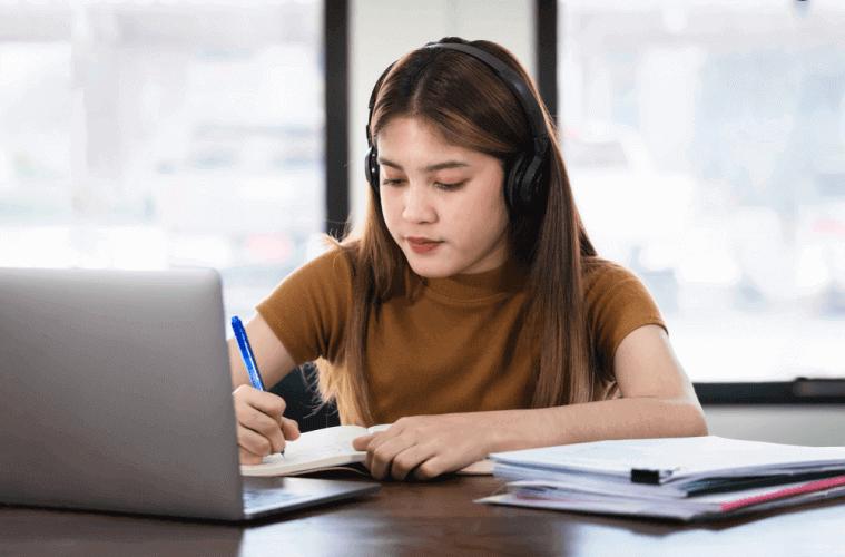 girl writing with headphones on
