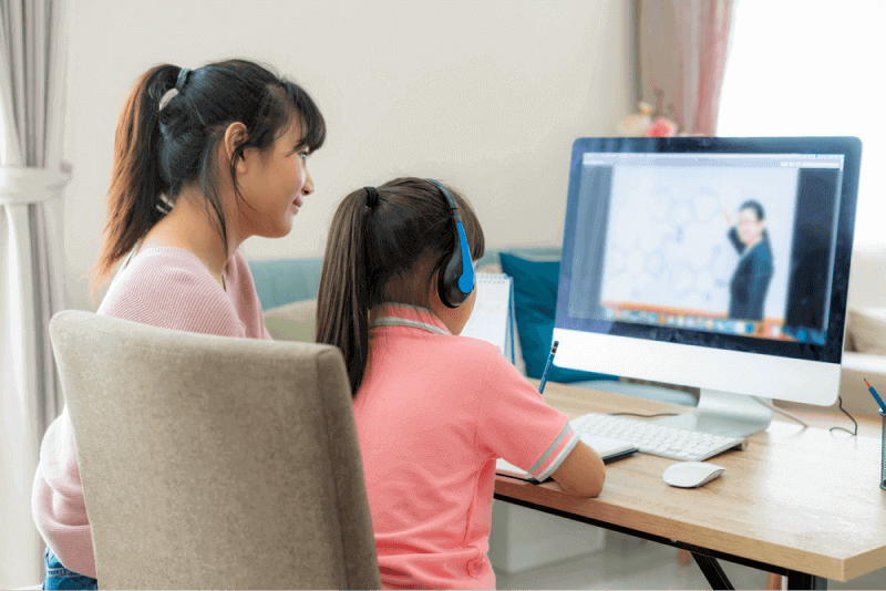 child and parent doing online learning